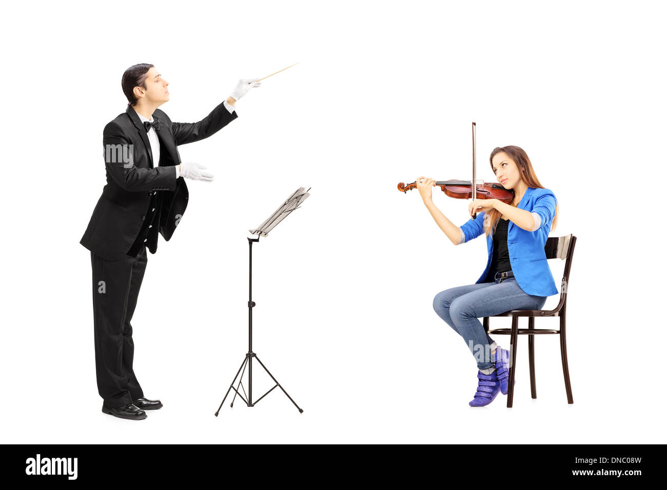 Male orchestra conductor directing a female playing violin - Stock Image