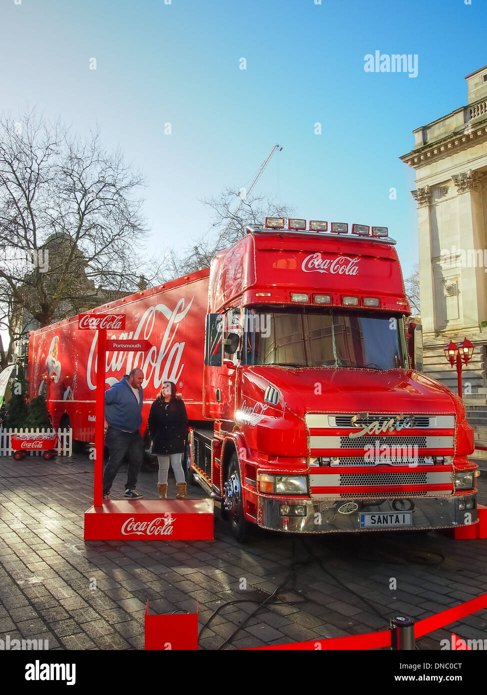 a couple prepare for a photograph with the Coca Cola Truck in front of Portsmouth Guildhall, Hampshire. England - Stock Image