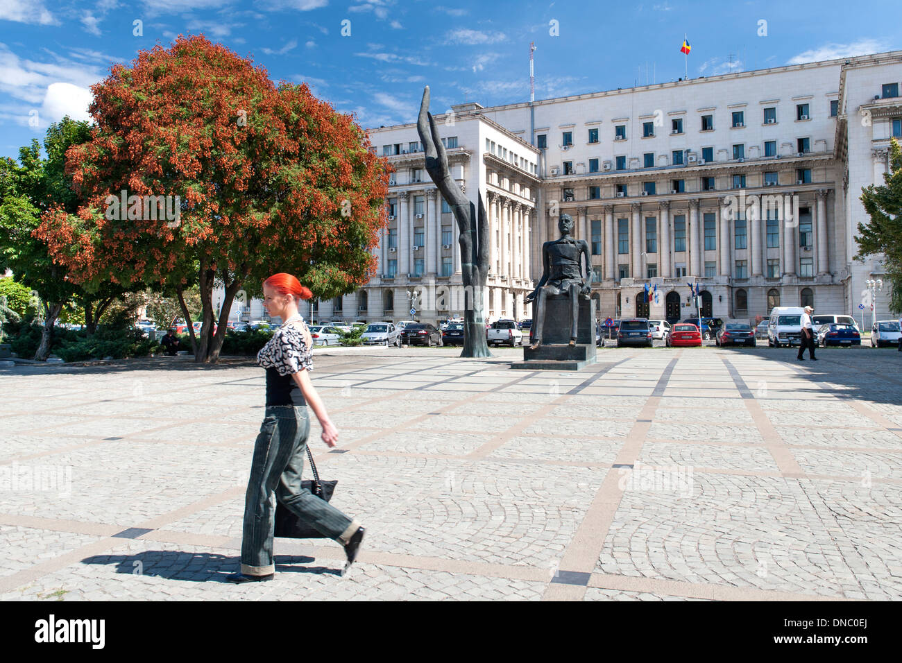 Woman walking through Revolution Square in Bucharest, the capital of Romania. - Stock Image