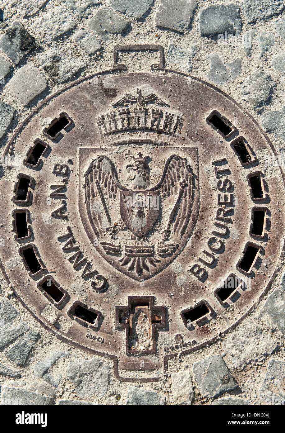 Manhole cover in Bucharest, the capital of Romania. It is inscribed with the coat of arms of the city. - Stock Image