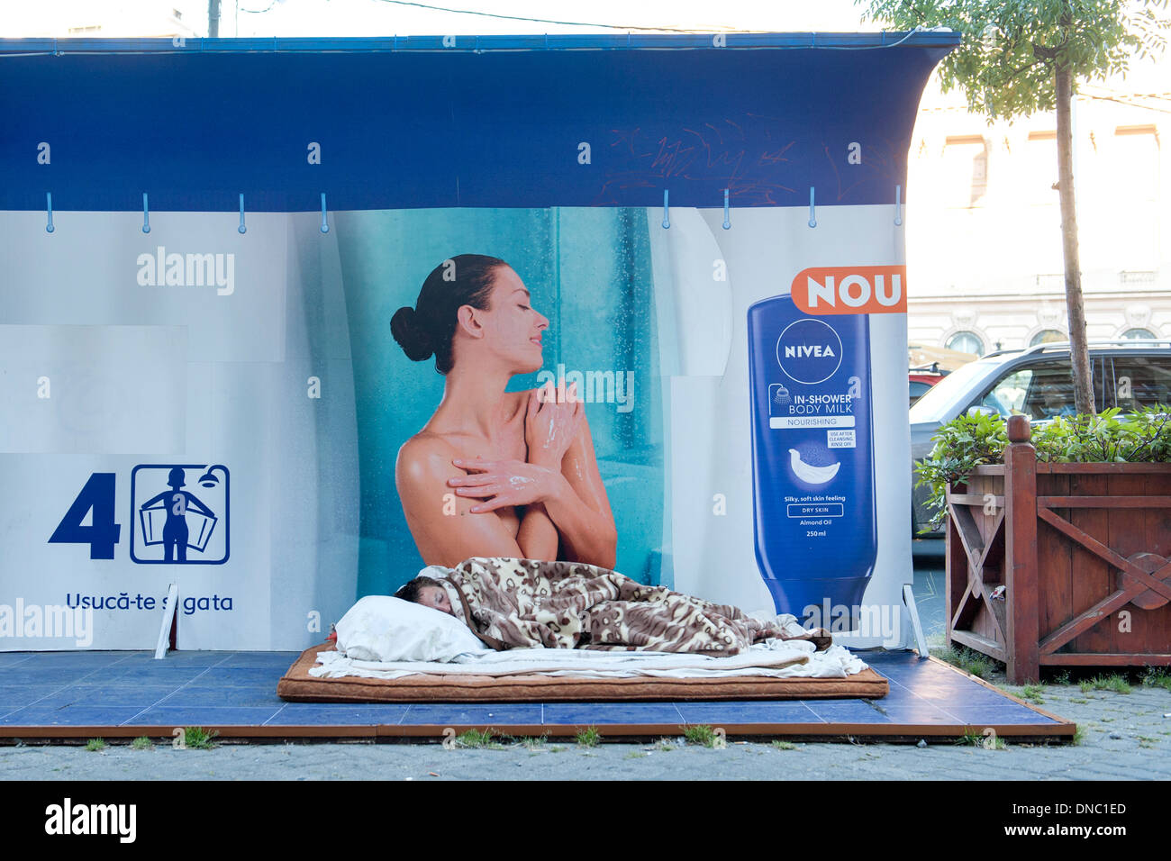 Homeless person sleeping in front of an advert for Nivea in Bucharest, the capital of Romania. - Stock Image