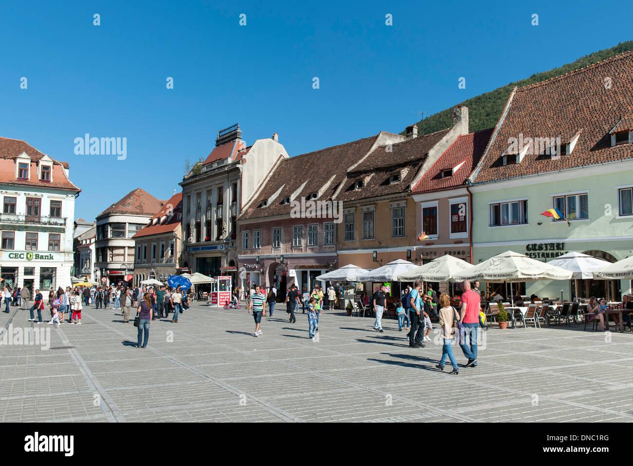 Pedestrians in Brașov Council Square (Piața Sfatului) in the old town in Brasov, a city in the Transylvania region of Romania. - Stock Image