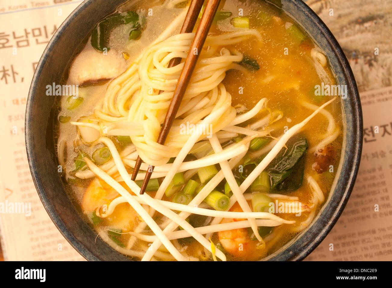 Close up of ramen noodle soup overhead with chopsticks - Stock Image