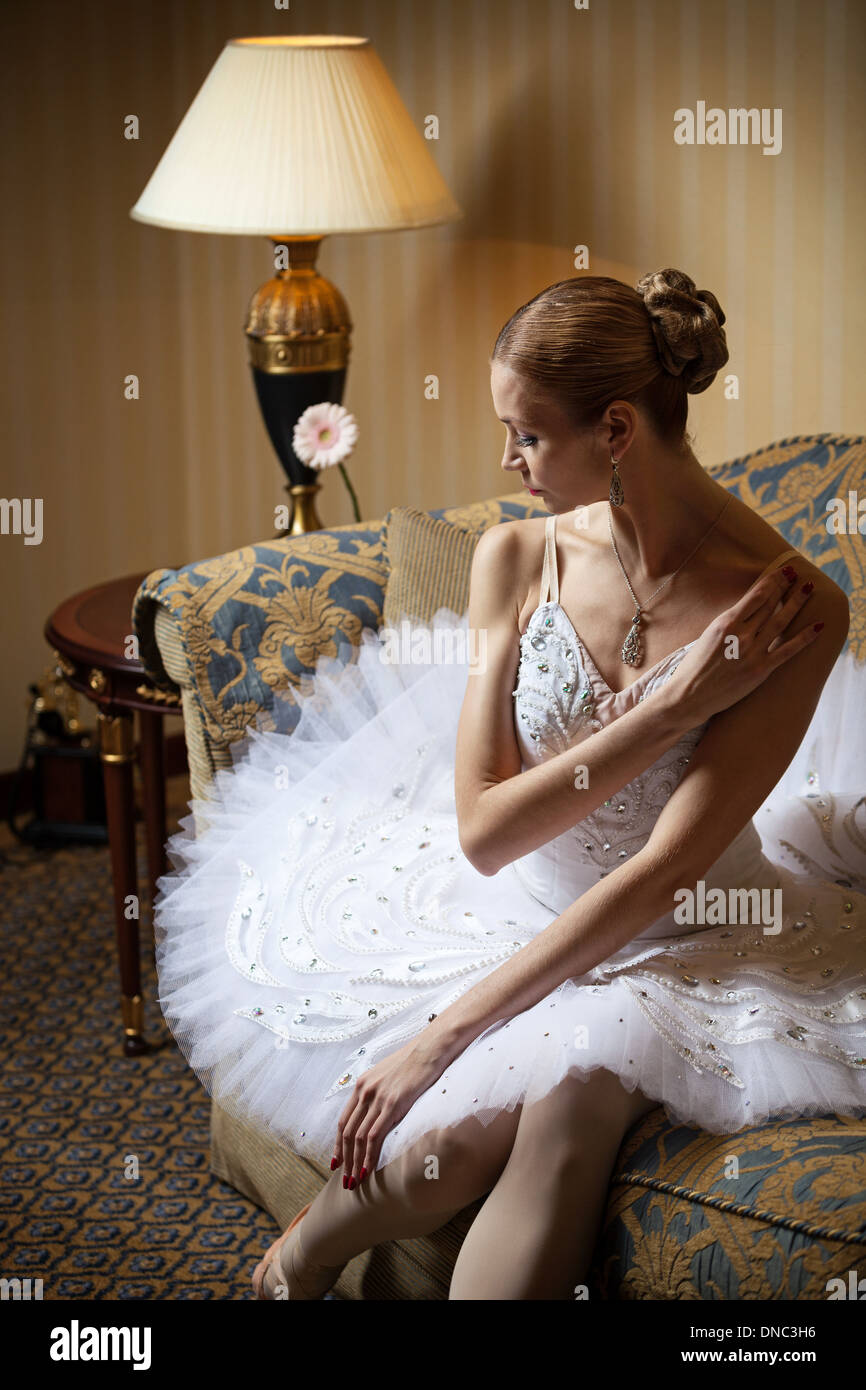 Professional ballet dancer sitting on sofa and looking down - Stock Image
