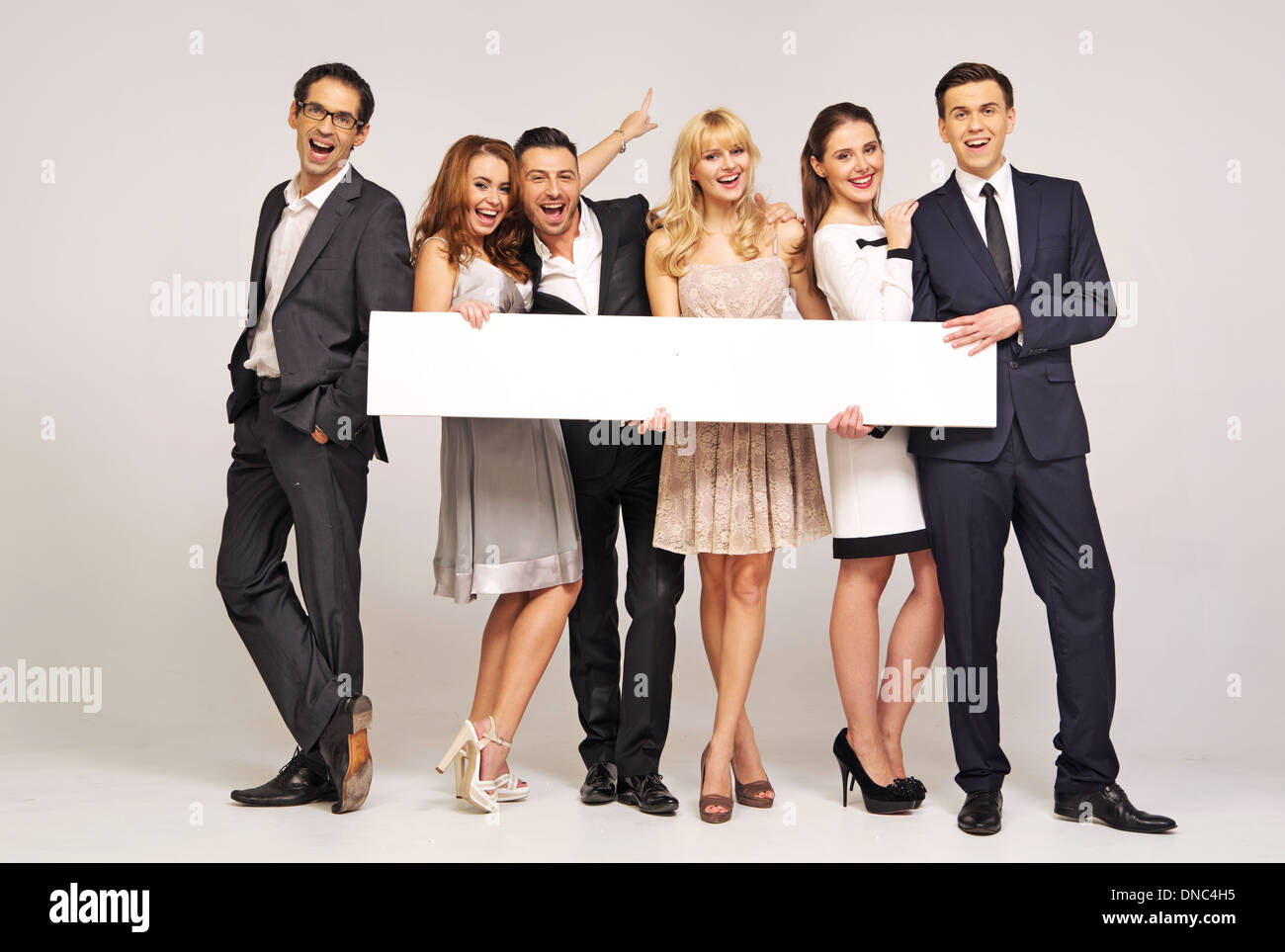 Laughing friends with empty white board - Stock Image