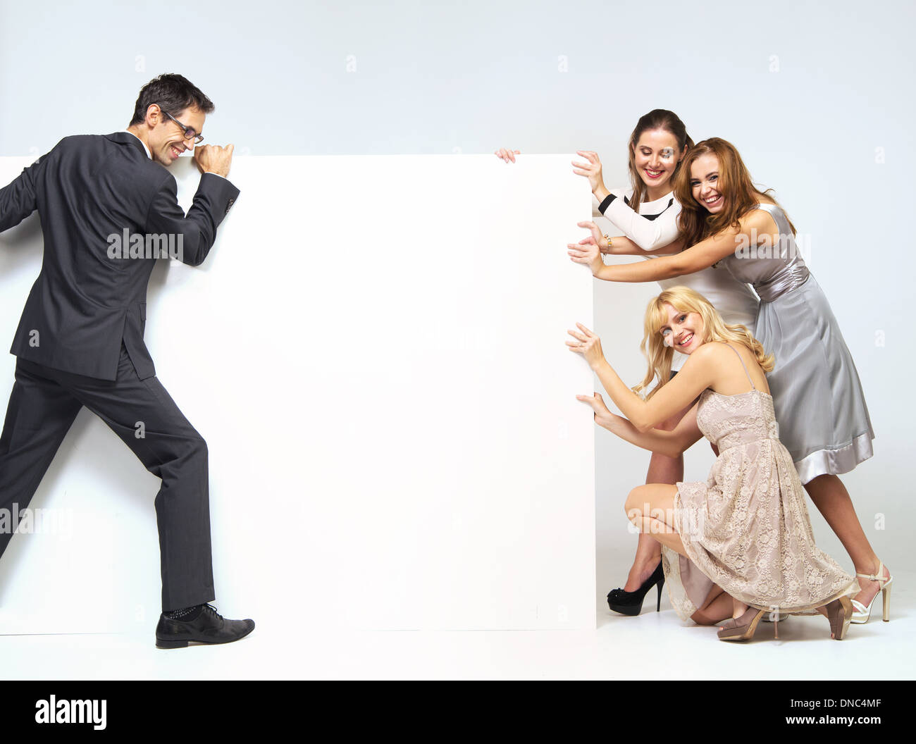 Man pushing through a board against young women Stock Photo