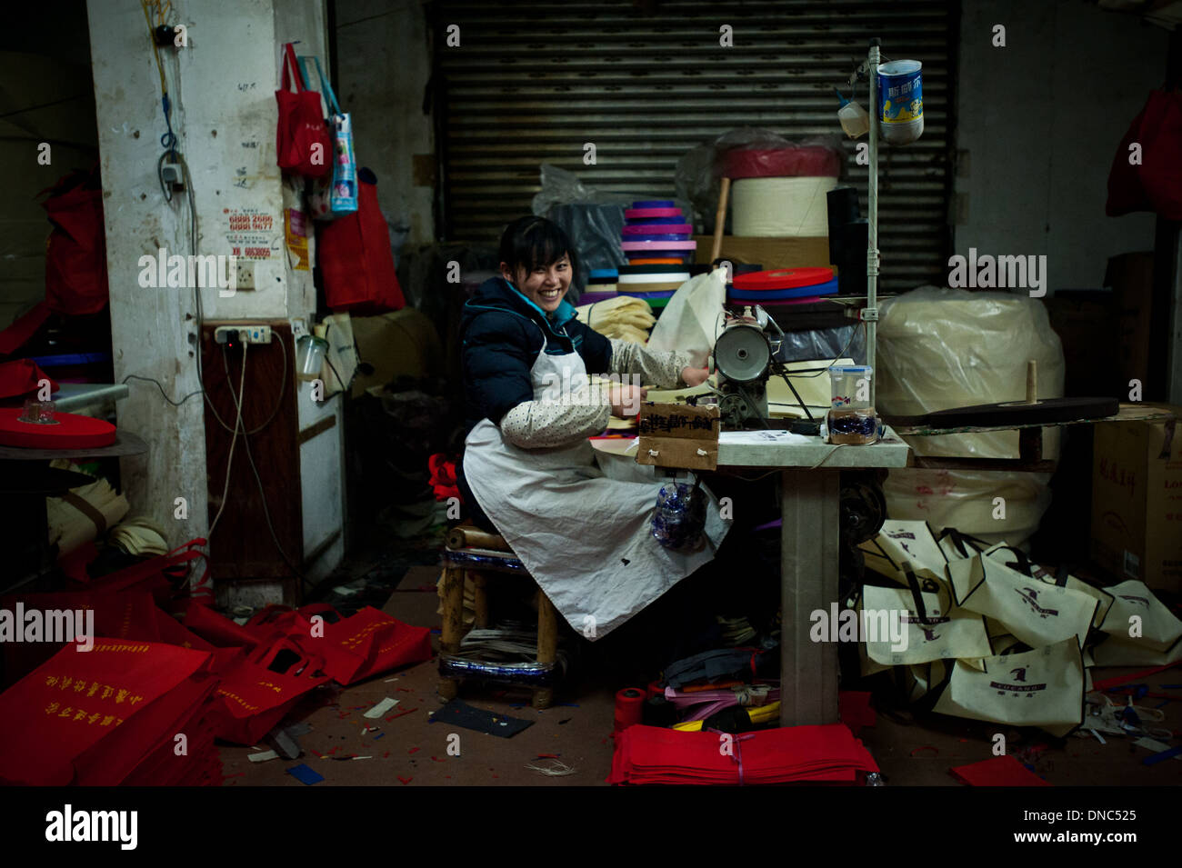 Chongqing, China - 31 December 2010: a woman smiles at the camera while working on a sewing machine in a messy textile factory - Stock Image