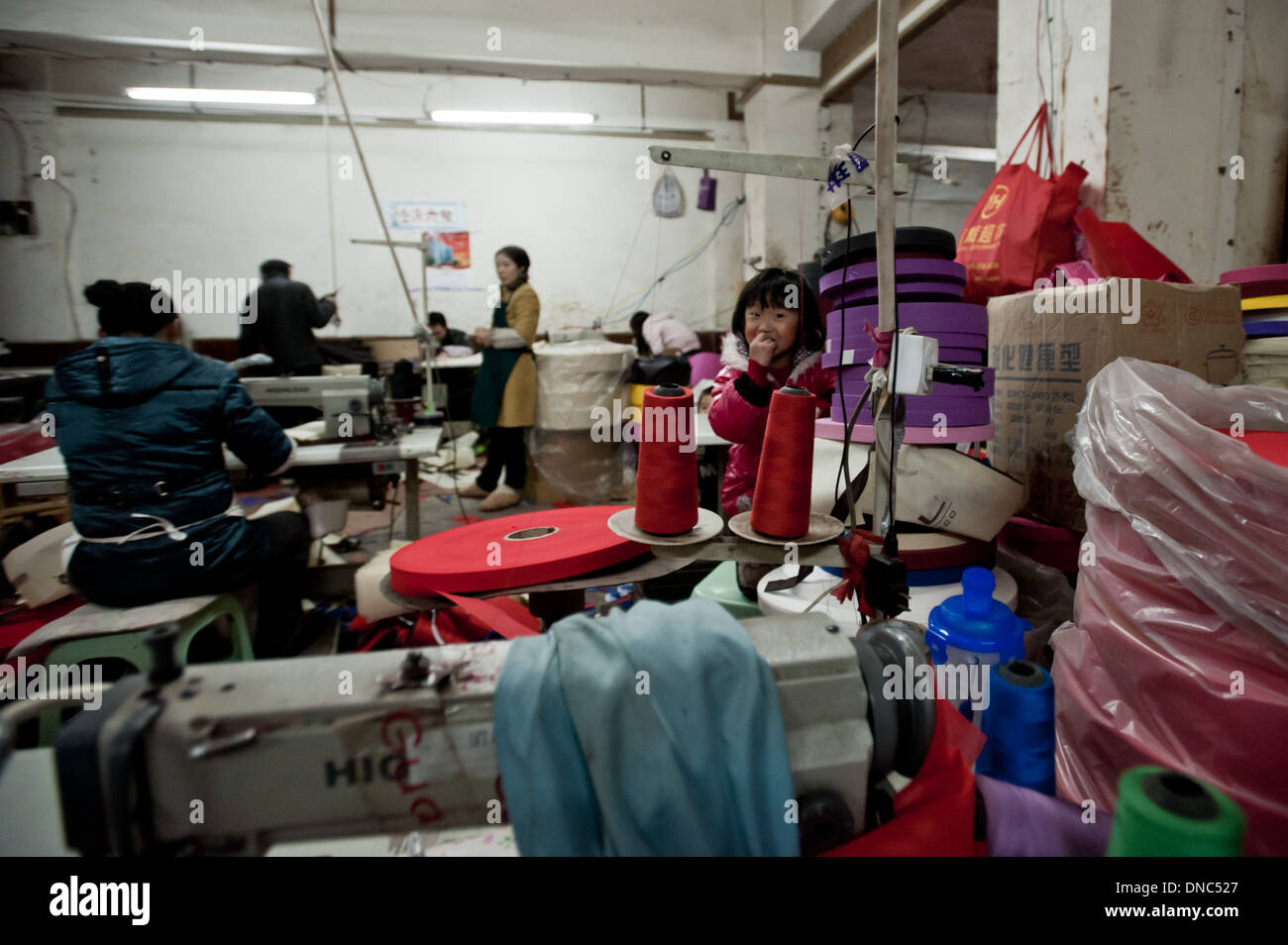 Chongqing, China - 31 December 2010: a child plays hiding behind textile materials while women work in a textile factory. The ch - Stock Image