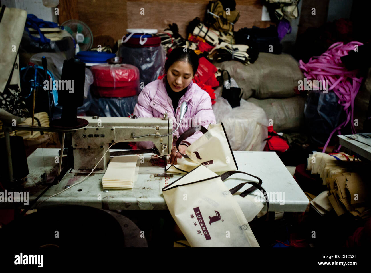 Chongqing, China - 31 December 2010: a chinese woman sews parts of a bag on a sewing machine in a textile factory. - Stock Image