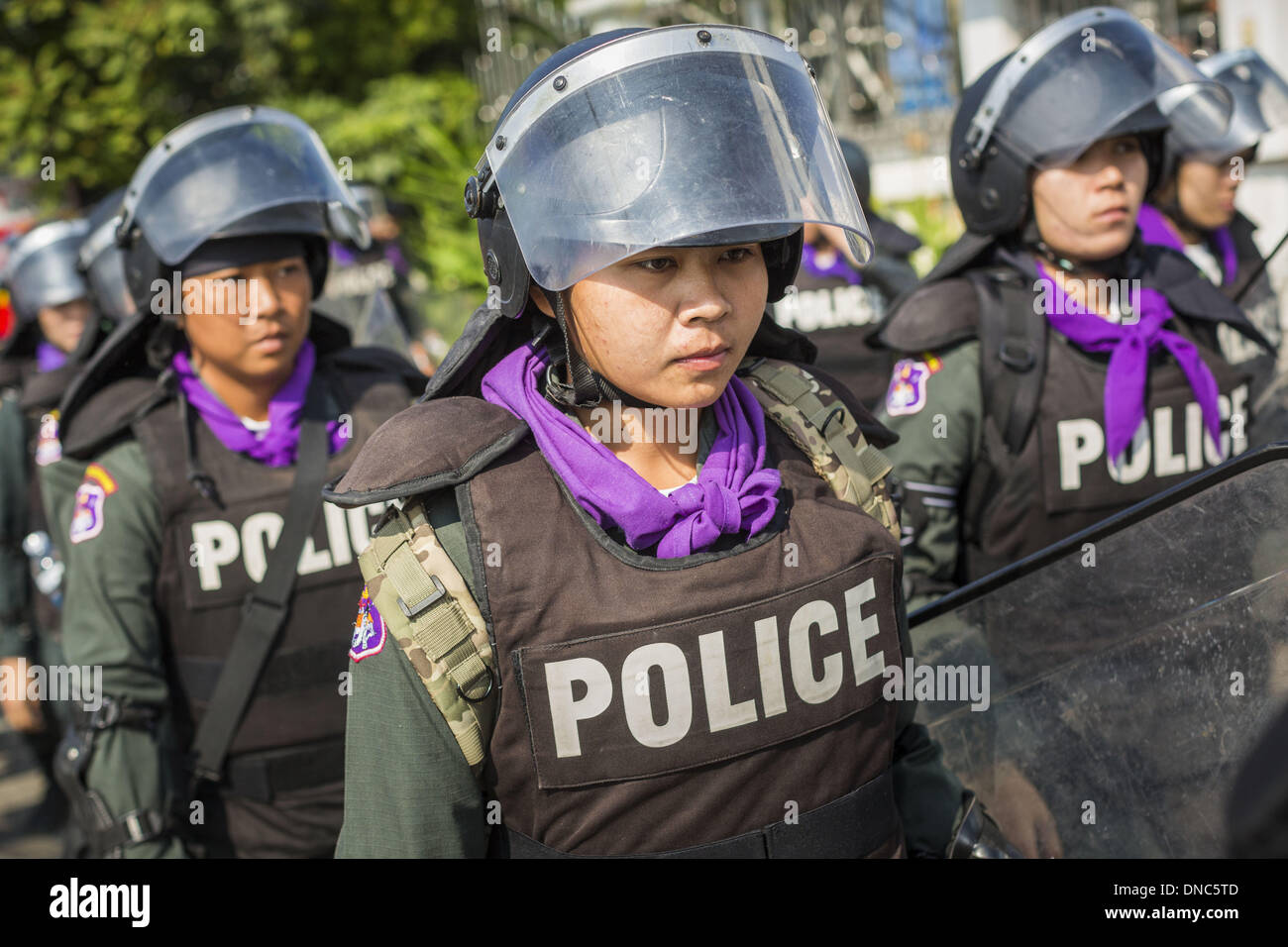 Bangkok, Thailand. 22nd Dec, 2013. Women Thai riot police retreat from a road block in front of the home of caretaker Stock Photo