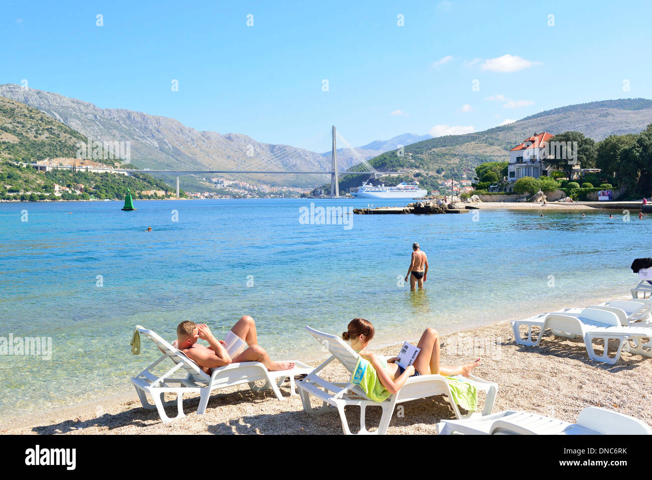 Sunbathers on Copacabana Beach, Dubrovnik and behind the Franjo Tuđman Bridge - cable-stayed bridge carrying the D8 state road - Stock Image