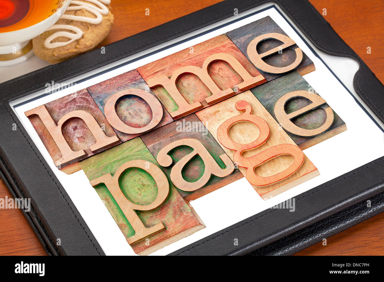 home page - text in letterpress wood type on a digital tablet with cup of tea - Stock Image