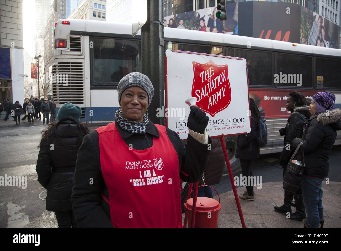 Volunteer woman raises money for the Salvation Army during the Christmas season at 34th Street and Broadway, NYC. - Stock Image