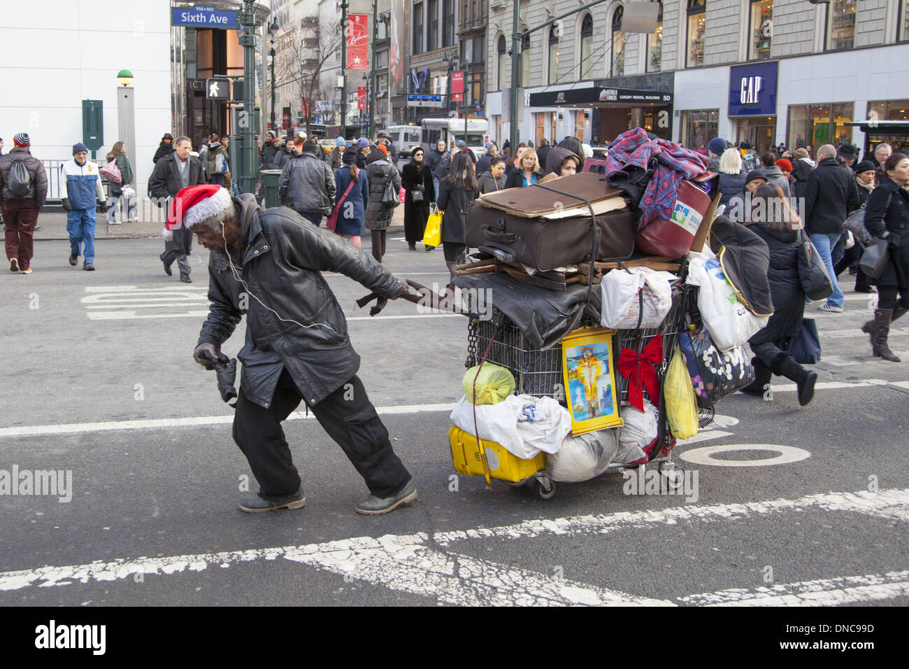 Homeless man in the Christmas spirit struggles up Broadway with his possessions in toe. - Stock Image
