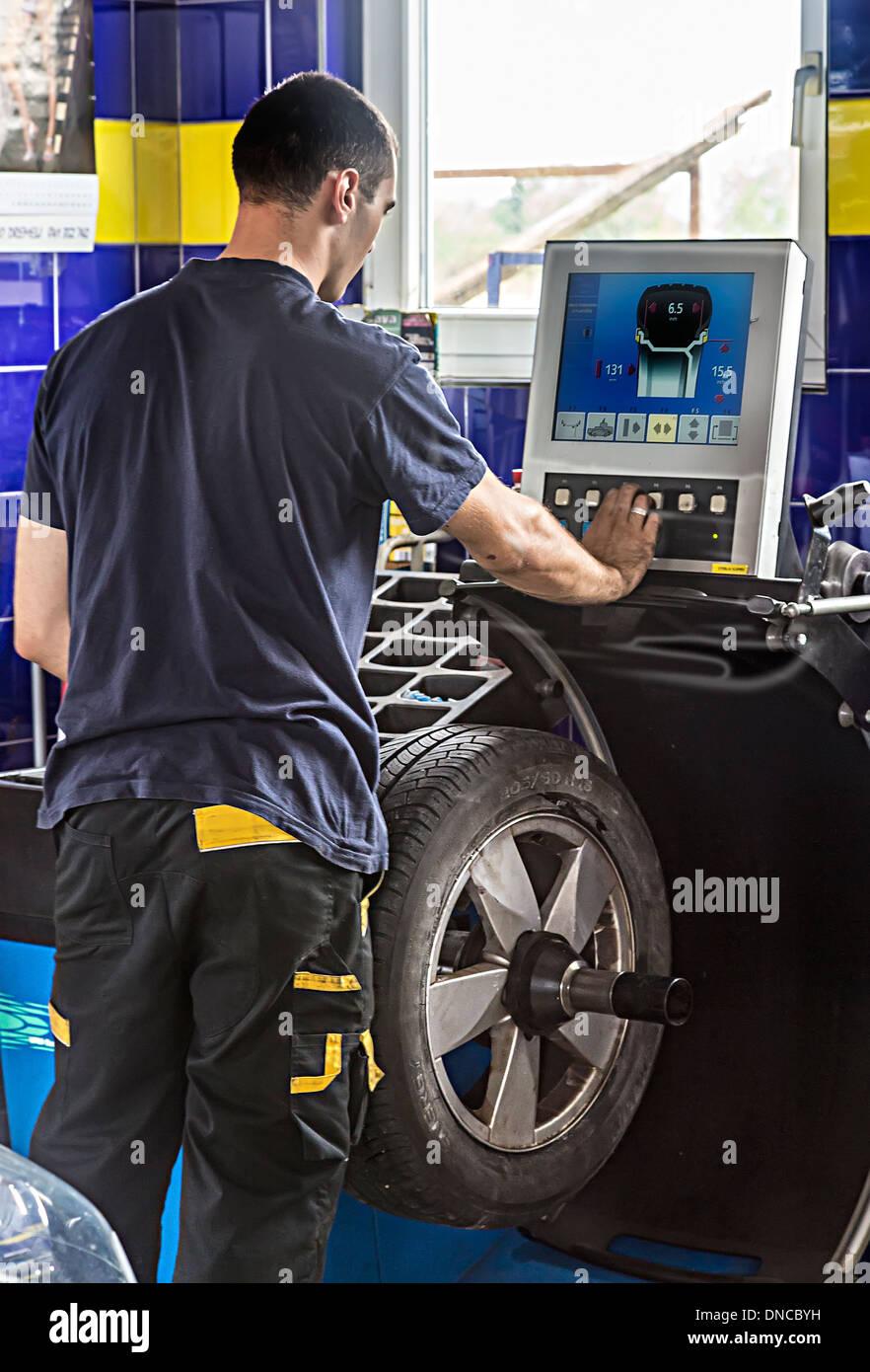 Mechanic in auto centre balancing new tyre on wheel, Slovenia - Stock Image