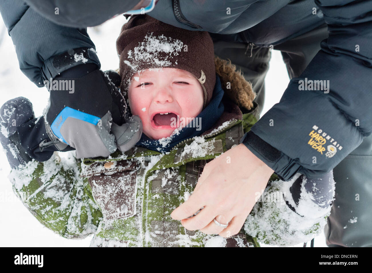 A 20 moth old baby boy crying after falling face first into snow - Stock Image