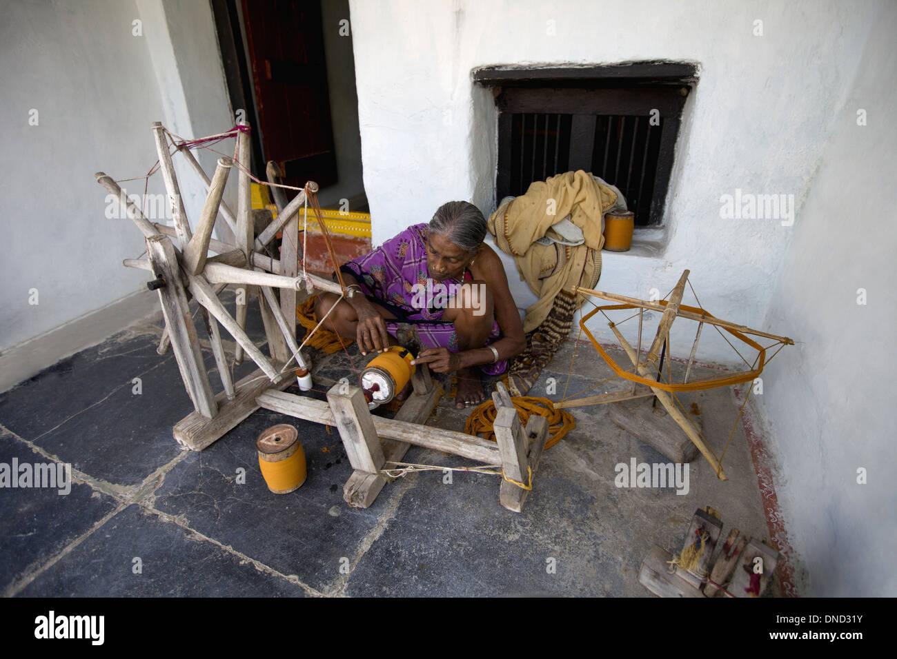 Tribal woman making thread on Charkha, the spinning wheel