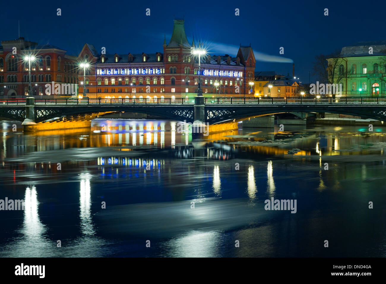 Winter night view of Vasabron and Riddarholmen, seen from Strömgatan, Stockholm.  Melting sheets of ice flow past Stock Photo