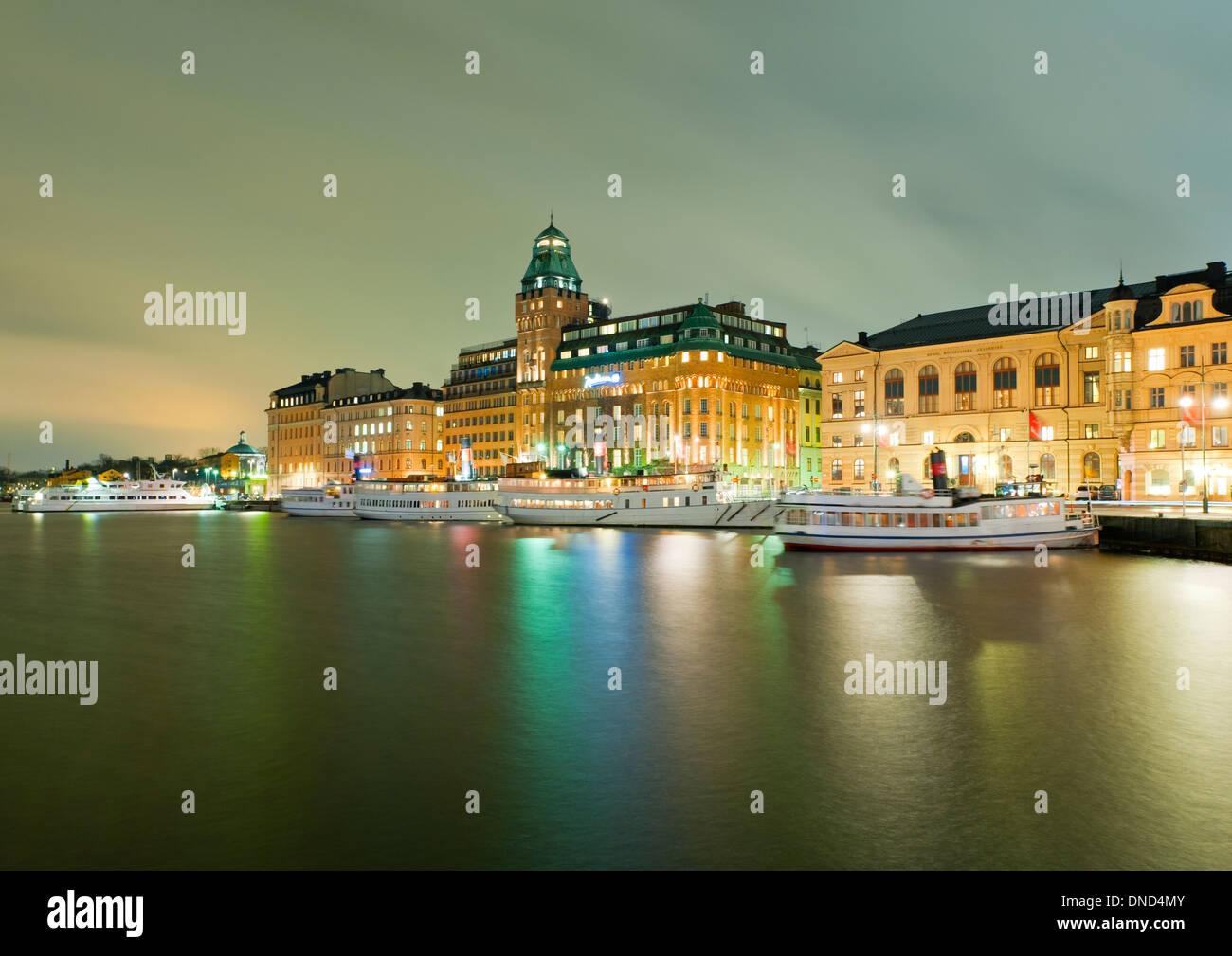Evening view across Nybroviken ('New Bridge Bay') towards Nybrokajen street and the Radisson Strand Hotel, Stockholm, Sweden. - Stock Image