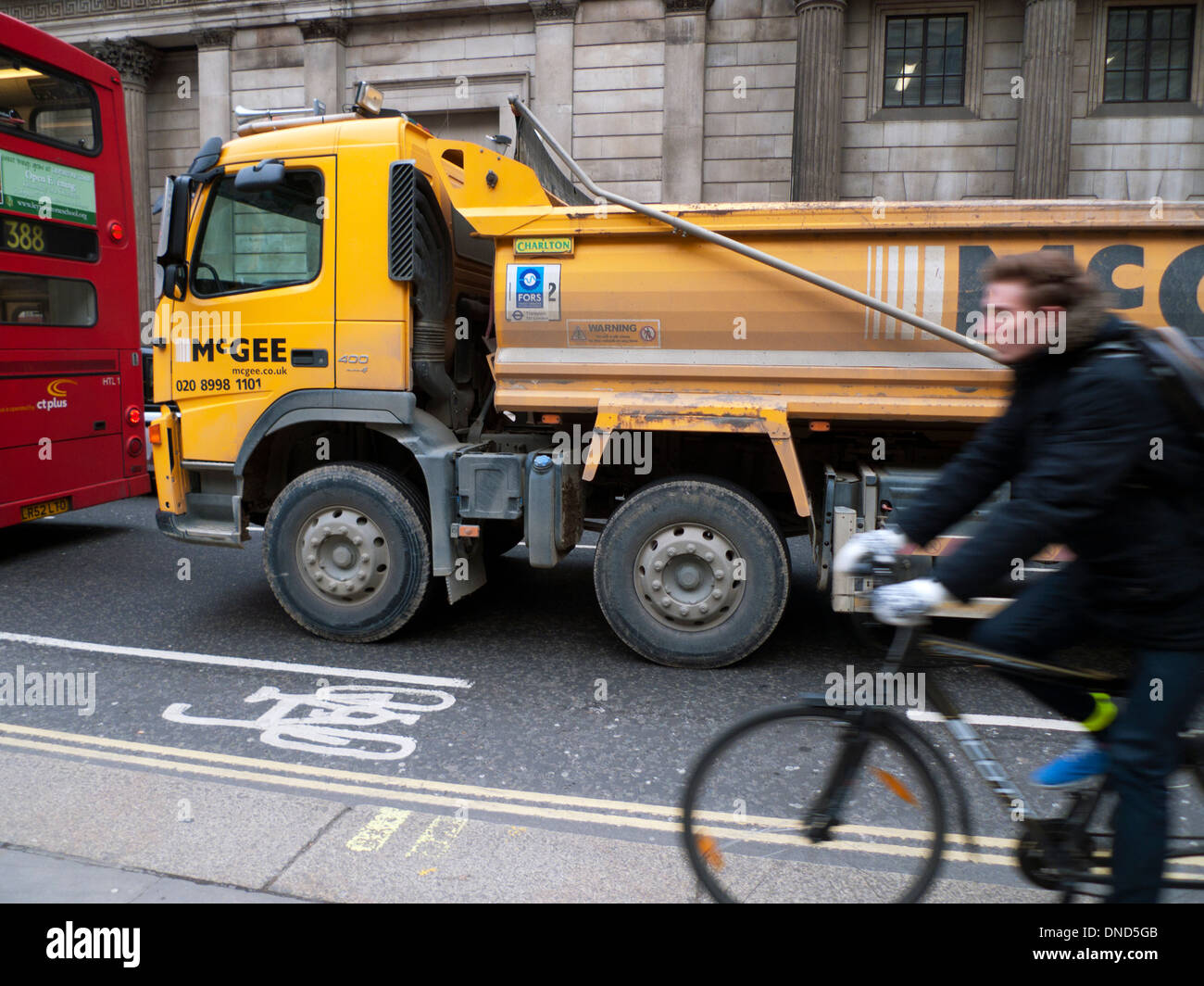 Man cyclist person cycling on pavement not in bike bicycle lane in heavy traffic near  HGV lorry and red double-decker bus London UK KATHY DEWITT - Stock Image