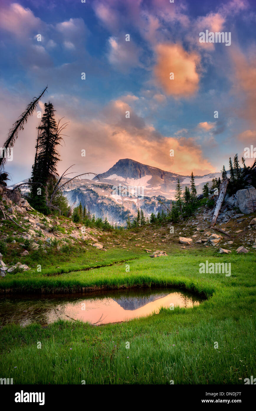 Small pond reflecting Eagle Cap Mountain and sunset clouds. Eagle Cap wilderness, Oregon - Stock Image
