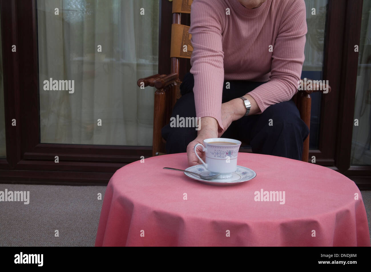 Elderly woman sitting in chair reaching out for cup of tea on table in front - Stock Image