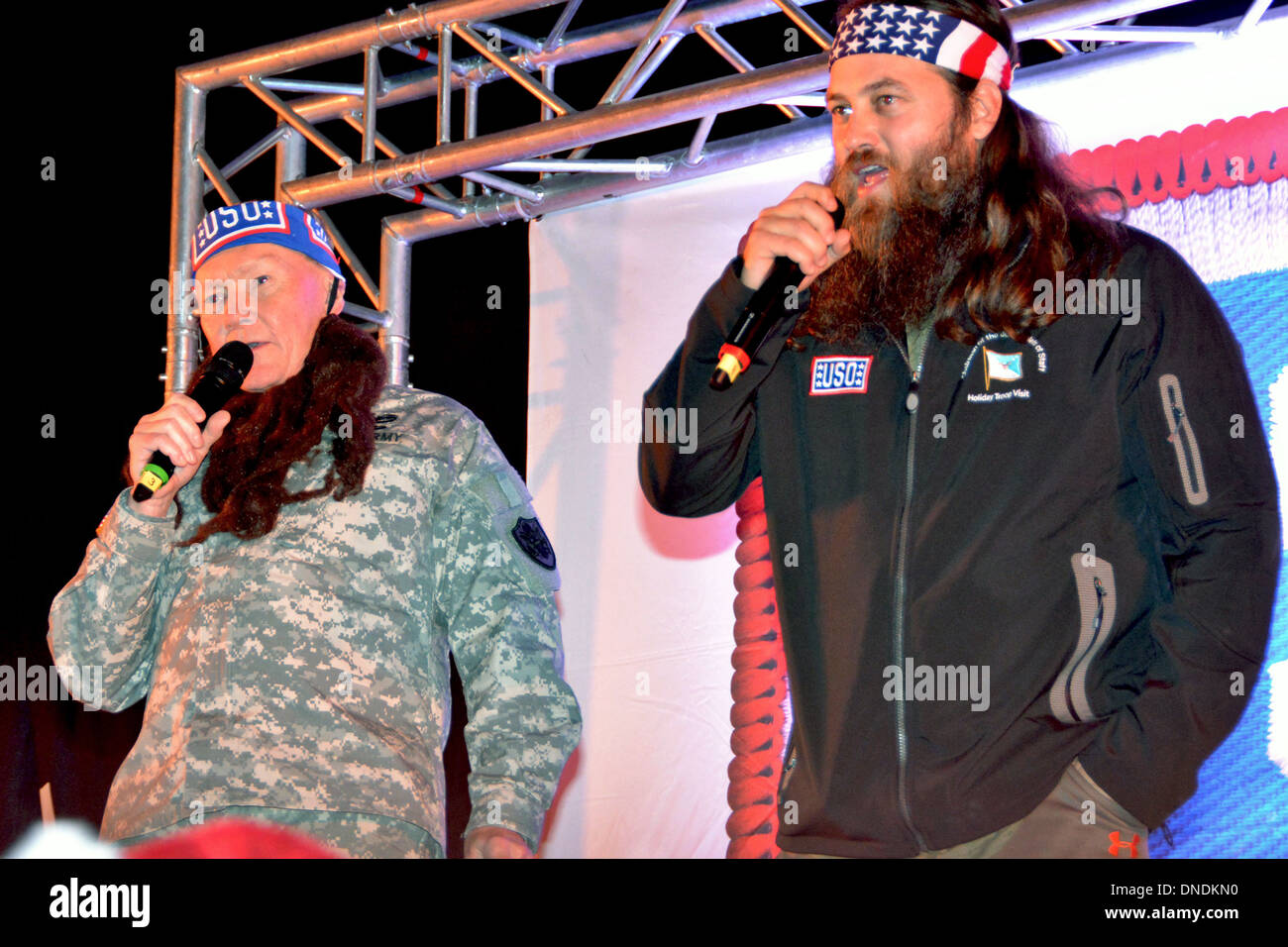 Chairman of the Joint Chiefs General Martin E. Dempsey, right, wears a fake beard as he sings a Christmas song with Duck Dynasty reality television star Willie Robertson December 12, 2013 at Wiesbaden, Germany. The visit was part of the USO Holiday Tour. - Stock Image