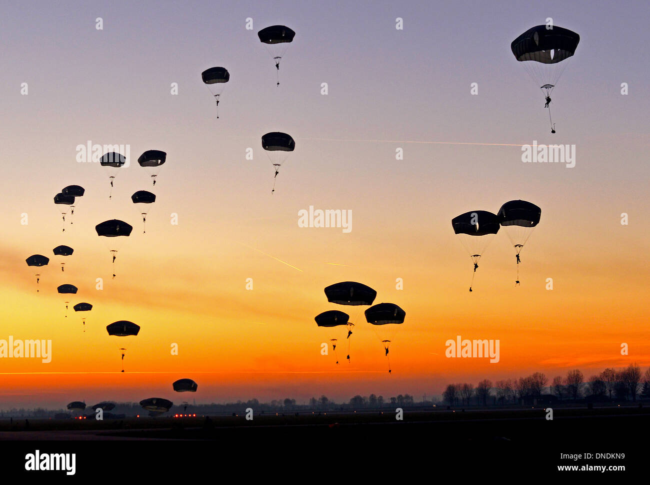 US Paratroopers drift down during a sunset parachute jump December 11, 2013 in Rivolta Air Force base, Italy. Airmen from Ramstein Air Base, Germany, and the 31st Fighter Wing at Aviano Air Base, Italy, partnered with soldiers from US Army at Vicenza to conduct airfield seizure training operations during a two-week close air support training exercise. - Stock Image