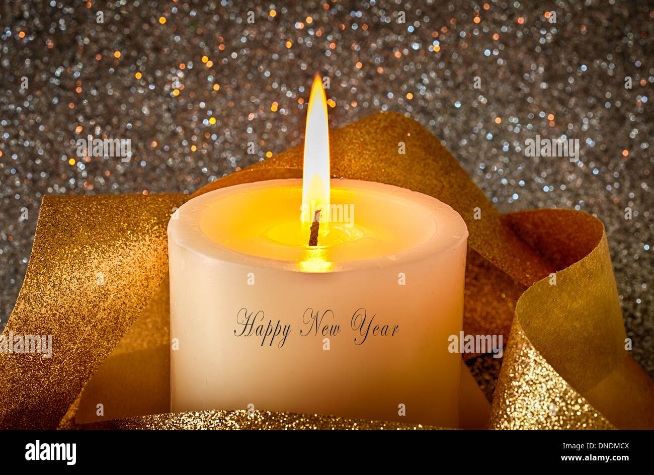 Candle with glitter and gold, and Happy New Year text - Stock Image