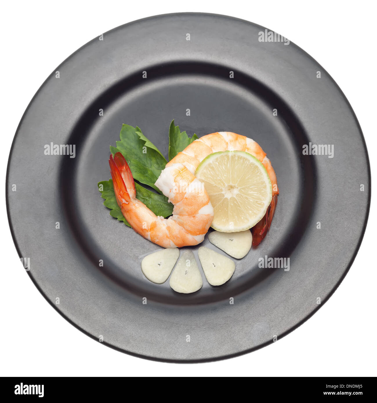 Shrimp with garlic and lime on black plate isolated on white backgorund Stock Photo