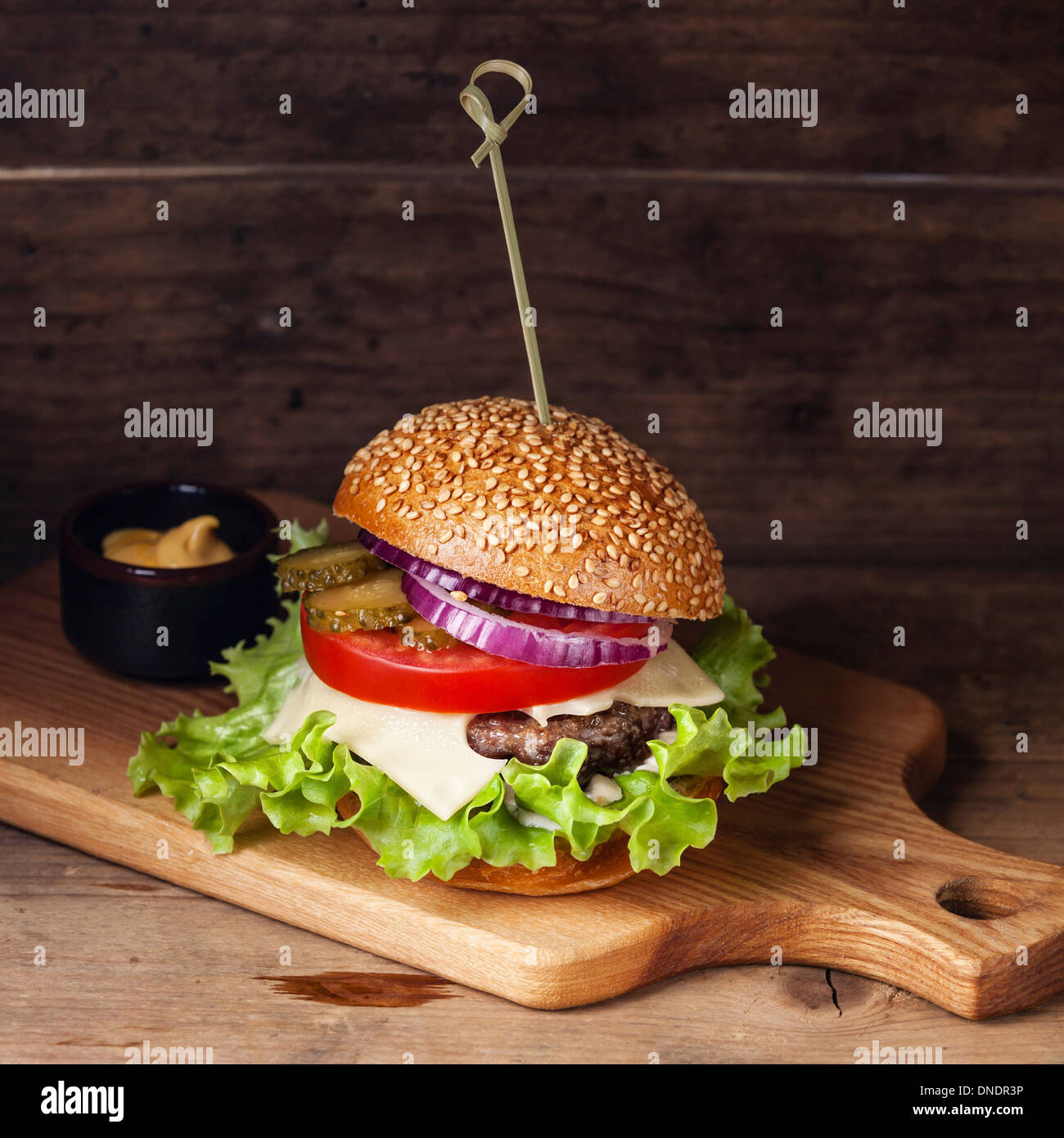 Burger with meat and greens wooden background - Stock Image
