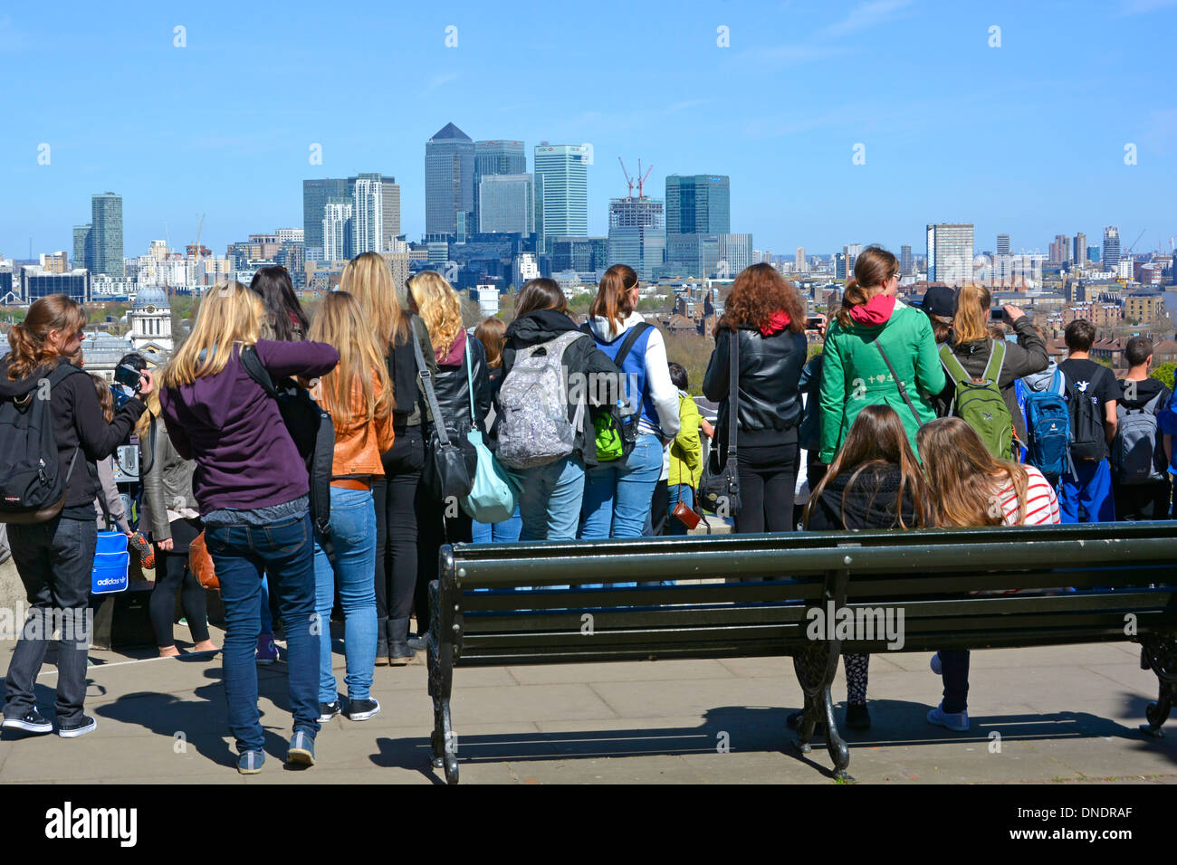 Group of girls & boys on educational visit to Greenwich park & Observatory looking at view towards Canary Wharf and the dome - Stock Image