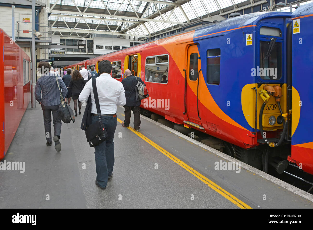 Commuters leaving South West Train service at London Waterloo Station terminus - Stock Image