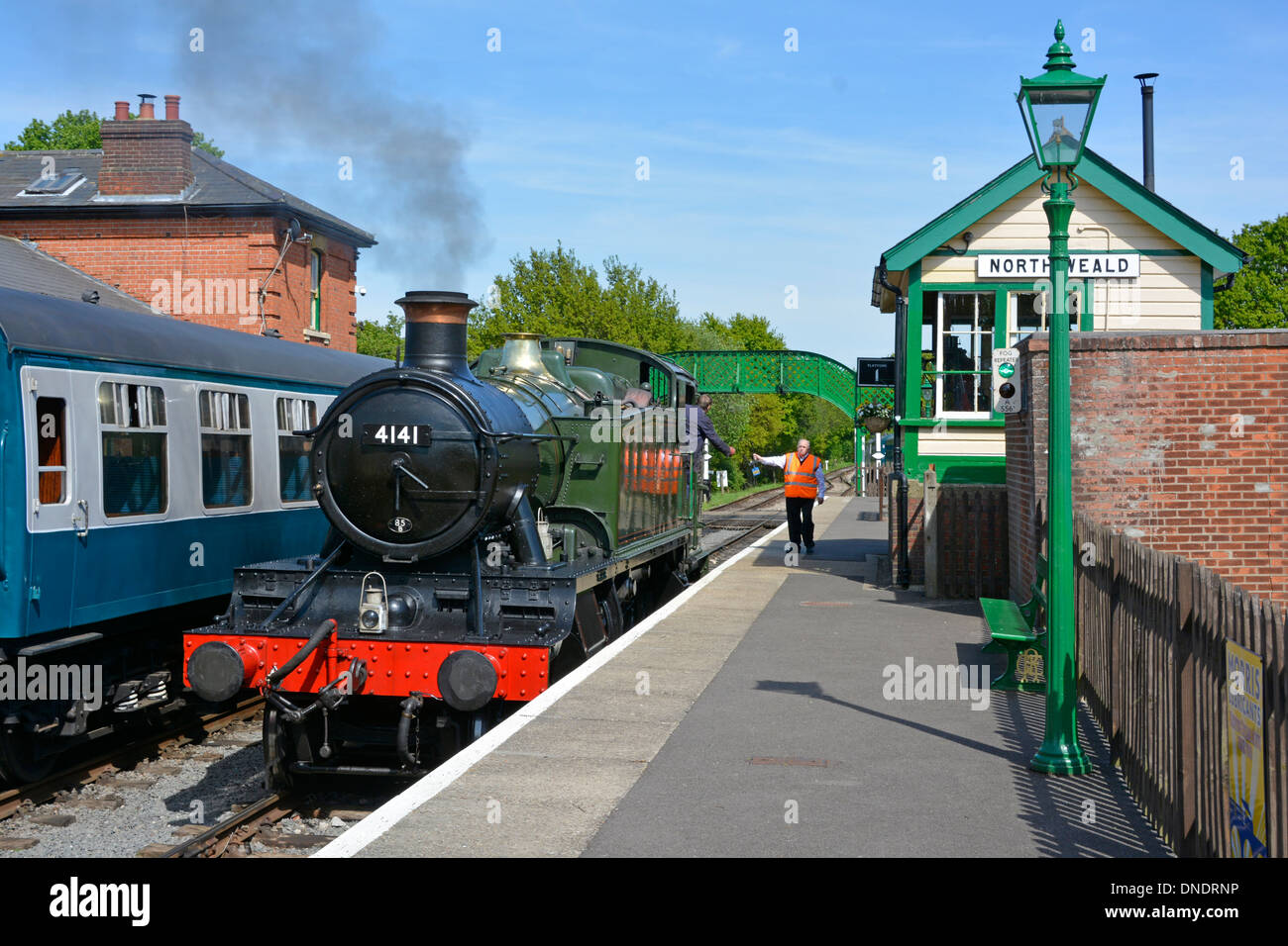 Signalman handing token to engine driver for single track working at North Weald signal box on the Epping Ongar heritage railway - Stock Image