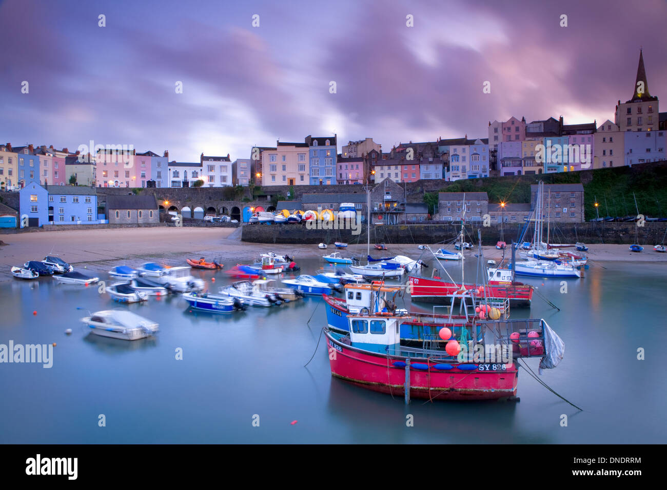 Tenby harbour with moored up Fishing boats. The town of Tenby with the flats and holiday homes are in the background Stock Photo