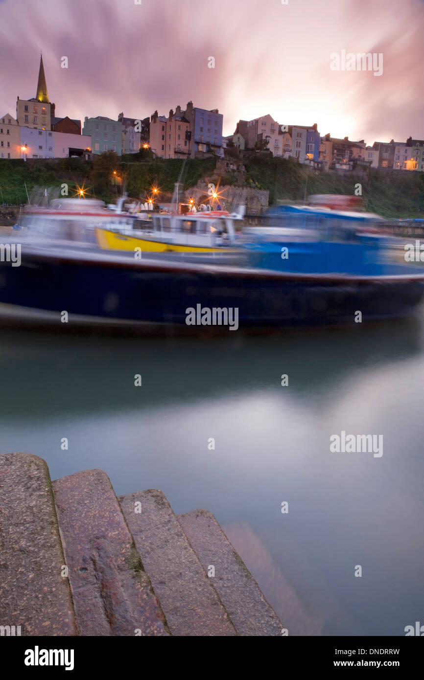 Fishing boats in the harbour at Tenby with the flats and holiday homes overlooking the sea in the background. Stock Photo