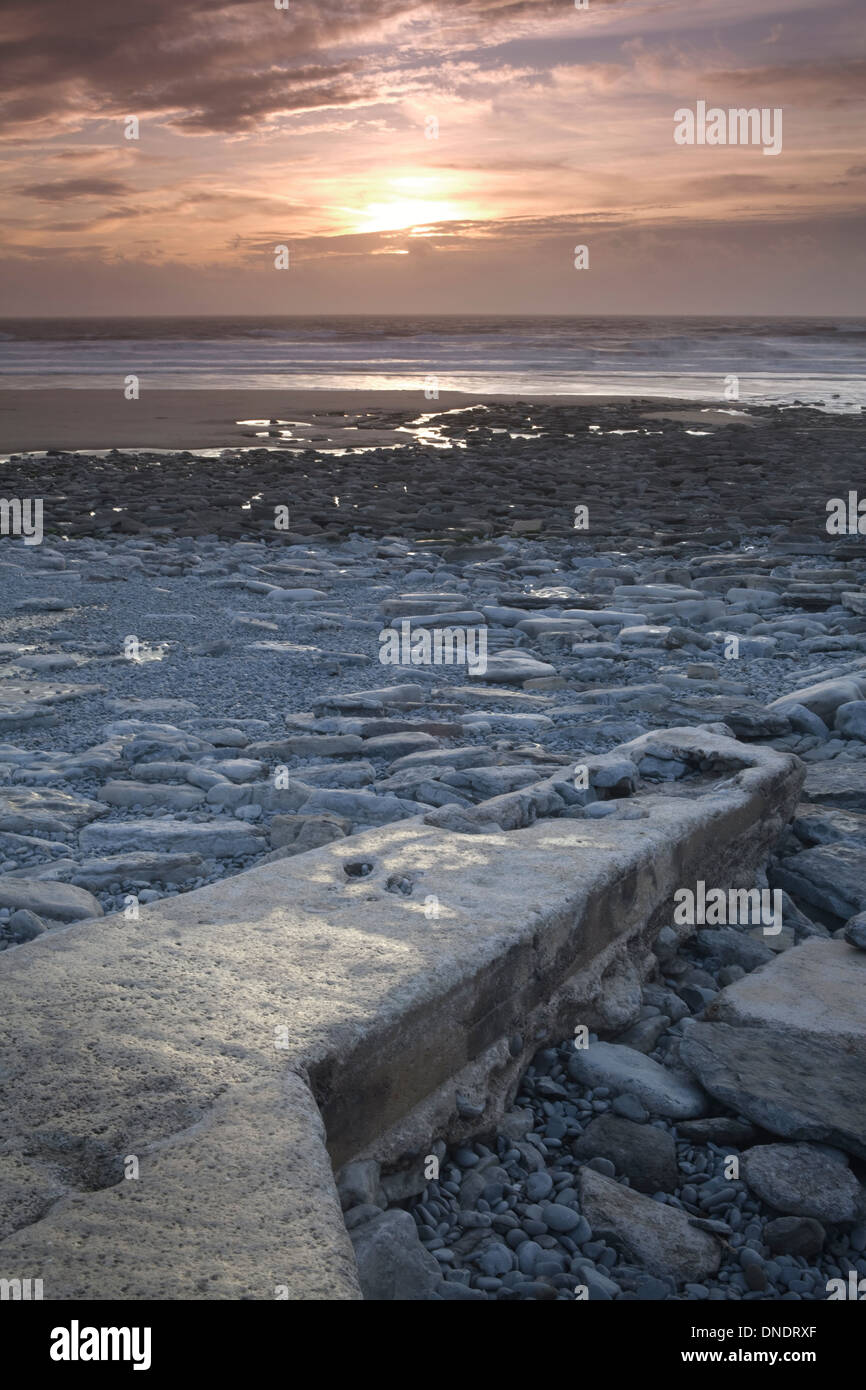 Rock formations at Dunraven Bay, South Wales, are caused by the power of the sea at sunset. Stock Photo