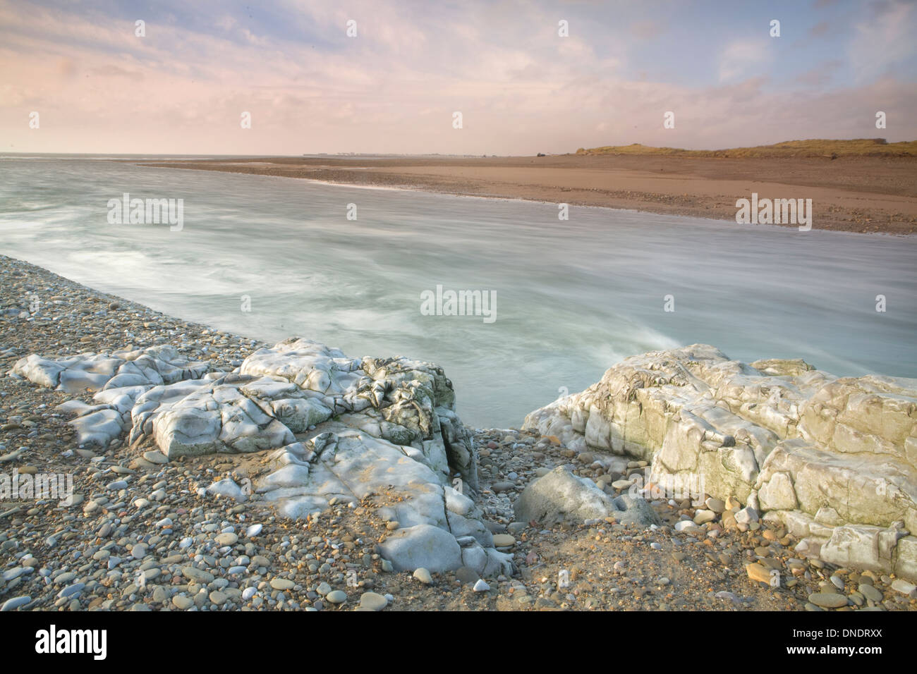 The River Ogmore, Afon Ogwr, reaches the sea at Ogmore-By-The-Sea. On side of the river is covered in pebbles and Stock Photo