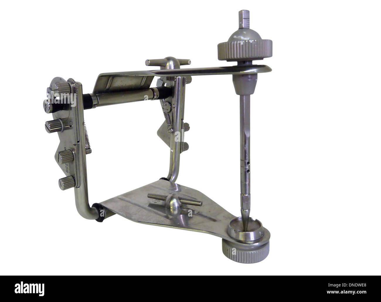 Grey metallic articulator used in dentistry. - Stock Image