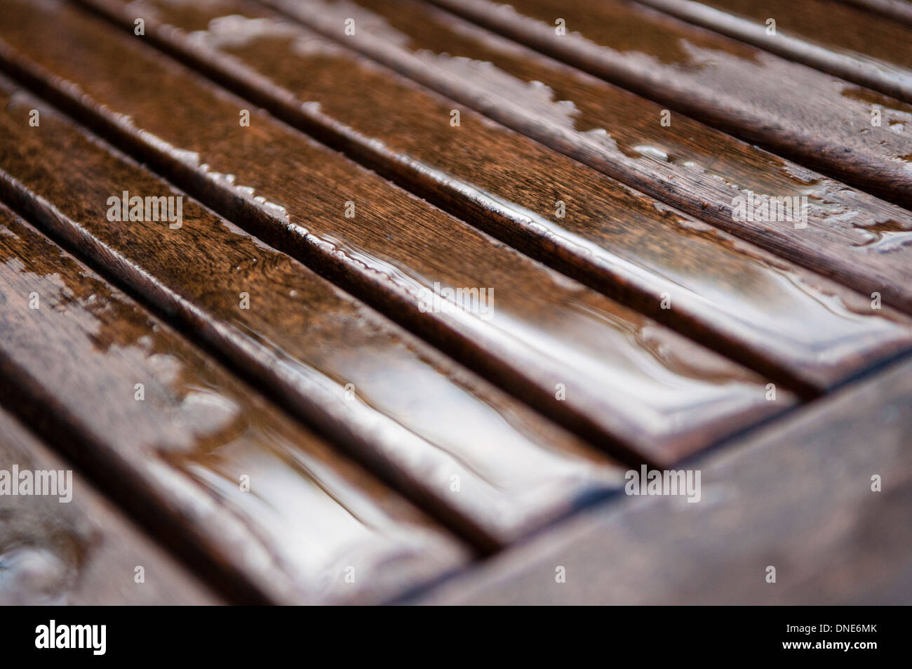 Close up of rainwater settled on varnished garden table top. - Stock Image