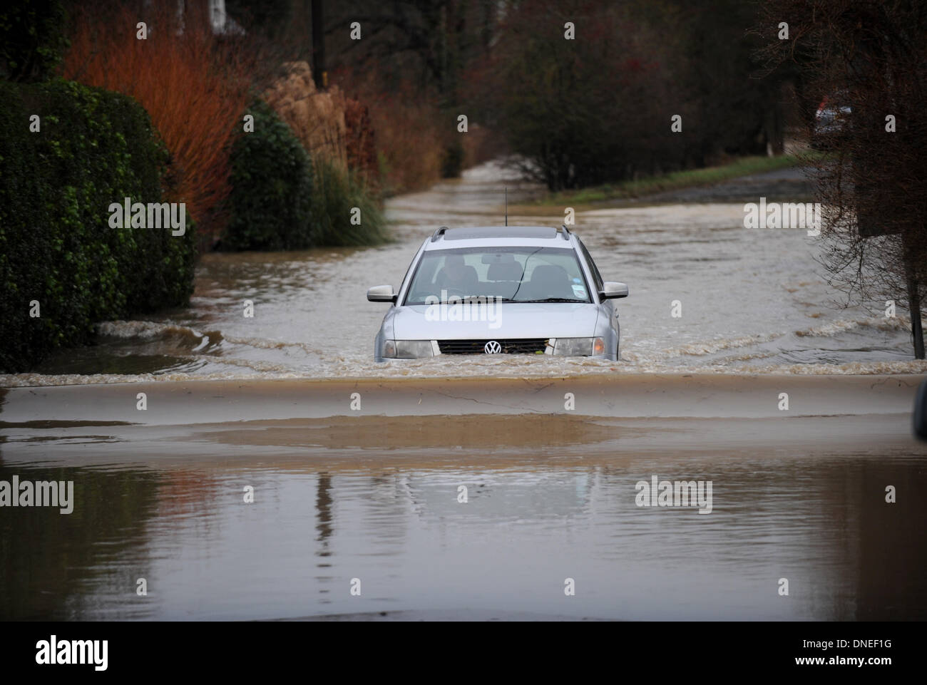 A car drives through flooded roads around the village of Barcombe near Lewes Sussex UK - Stock Image