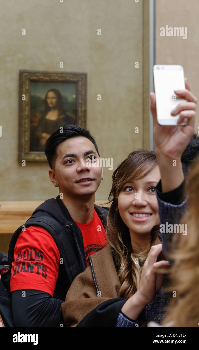 people taking selfie photos in front of the Mona Lisa painting by Leonardo da Vinci, Louvre Museum, Paris, France Stock Photo