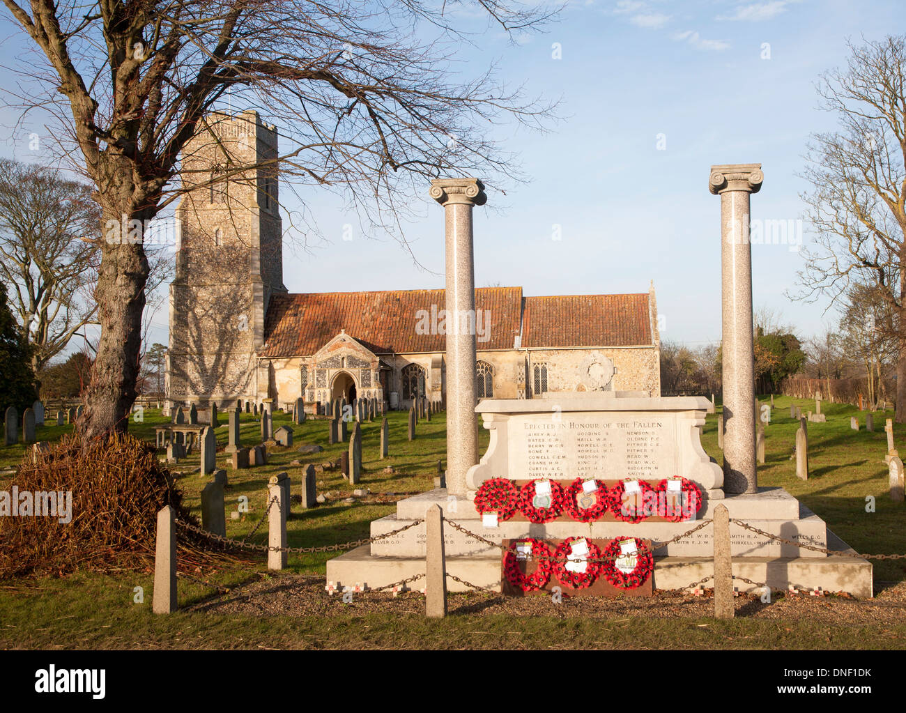 War memorial with poppy wreaths at St John the Baptists church, Snape, Suffolk, England - Stock Image