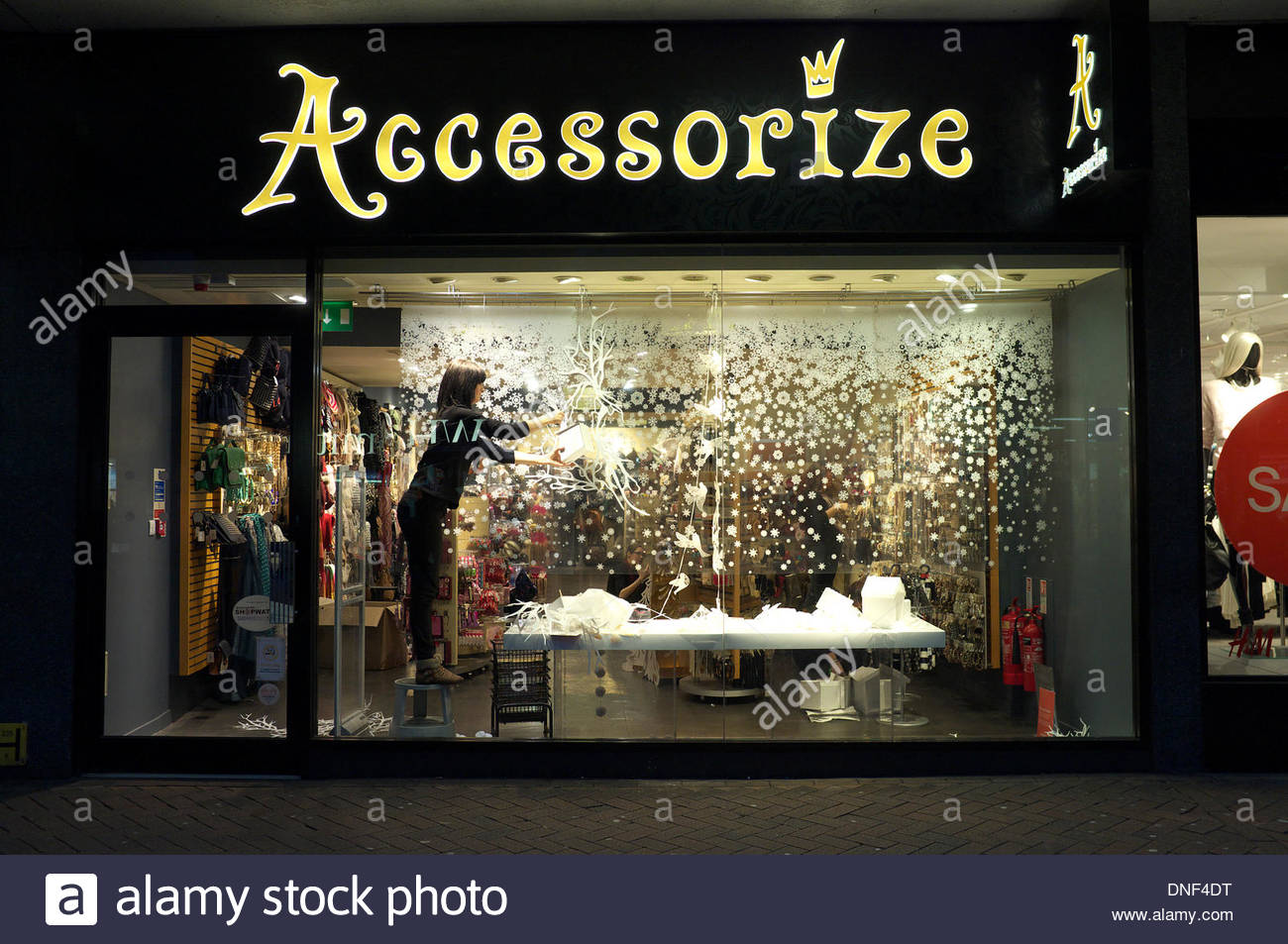 A shop worker removes Christmas decorations in the display window of retailer Accessorize, a fashion accessory retail chain. It is Christmas Eve and the last customers have left and the store is preparing to be ready for the Boxing Day sales. Gloucester, UK, 24th December 2013. - Stock Image