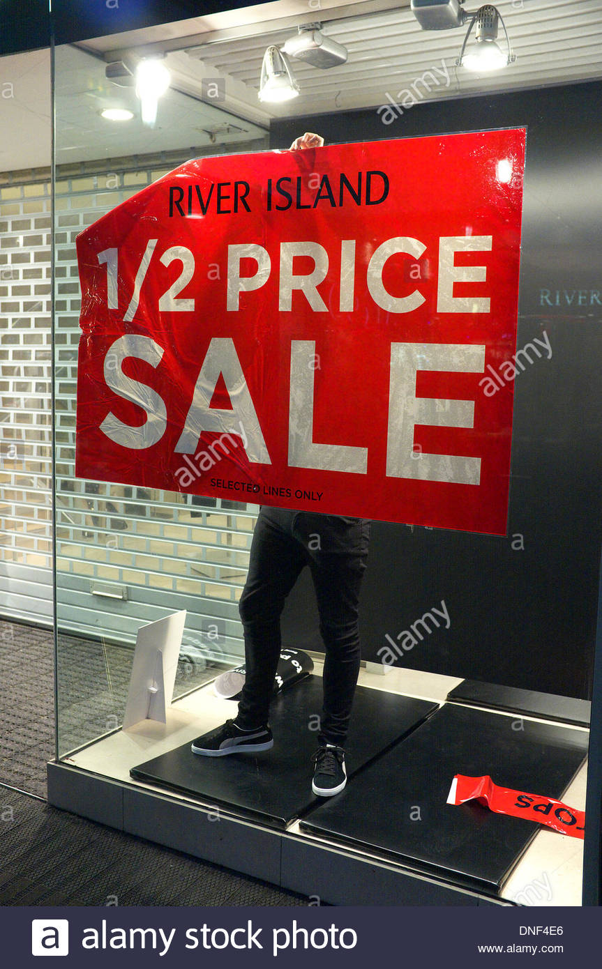 Gloucester, UK. 24th December 2013. A shop worker puts up a '1/2 PRICE SALE' poster in the display window of River Stock Photo