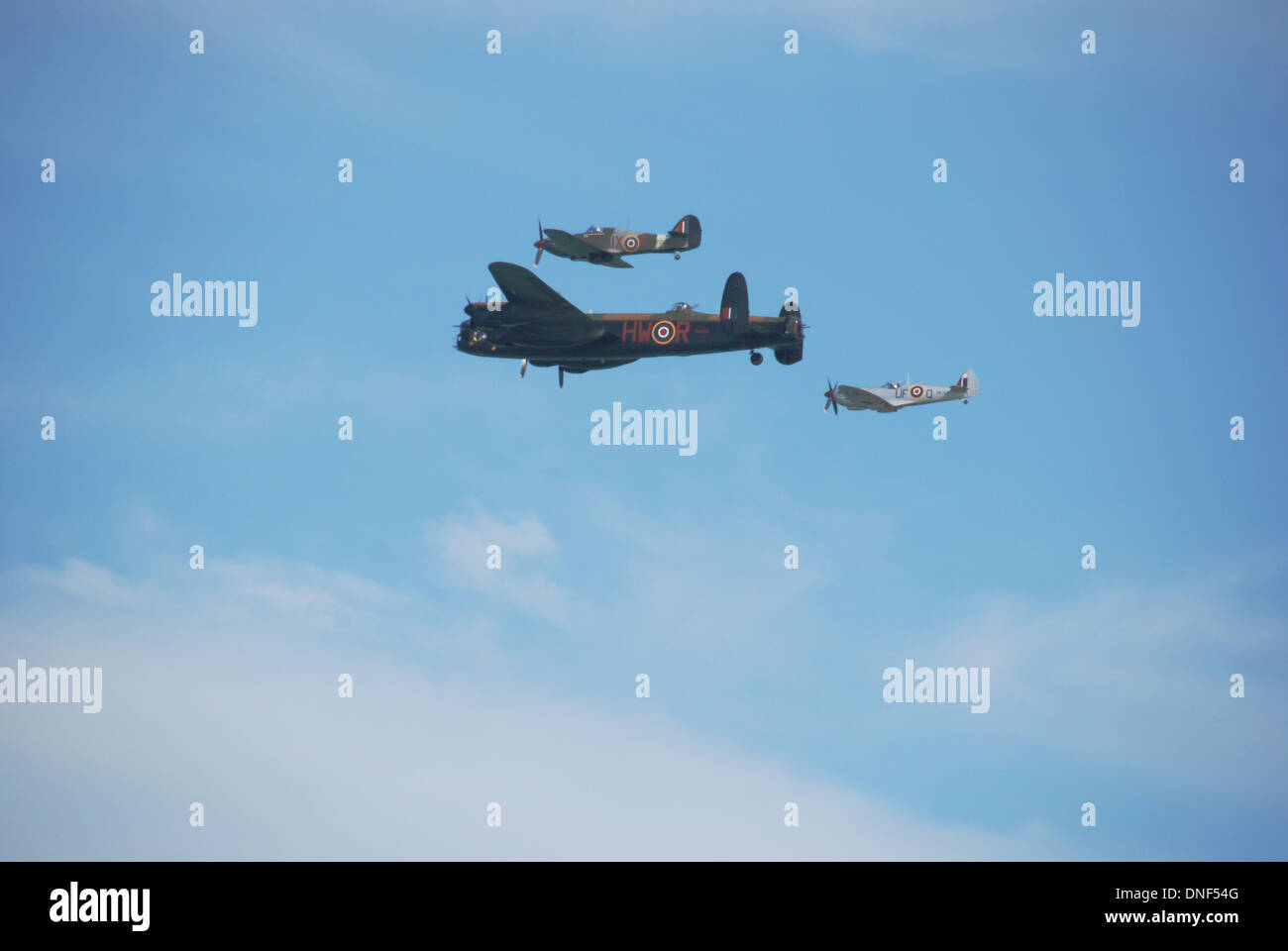 WWII Spitfire, Hurricane and Lancaster Bomber formation flight against blue sky clouds - BBMF- Battle of Britain Memorial Flight - Stock Image