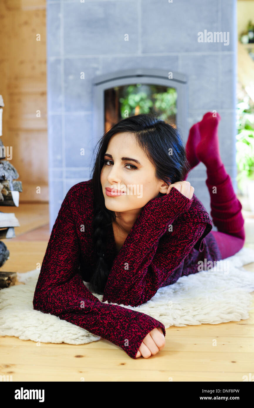 young, beautiful woman heating in living room (model-released) - Stock Image