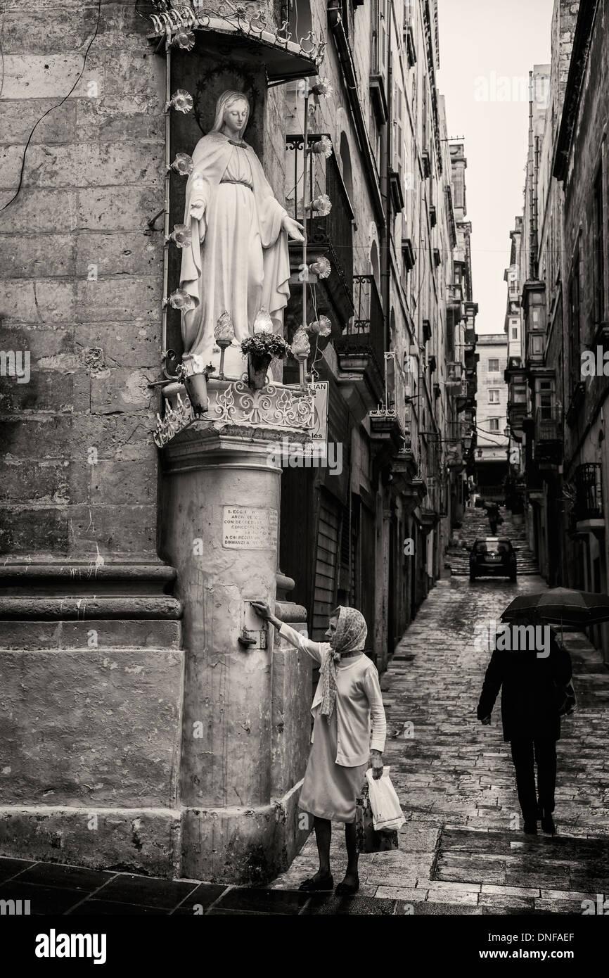 Lady makes a donation to a shrine on a street corner, Valletta, Malta. - Stock Image