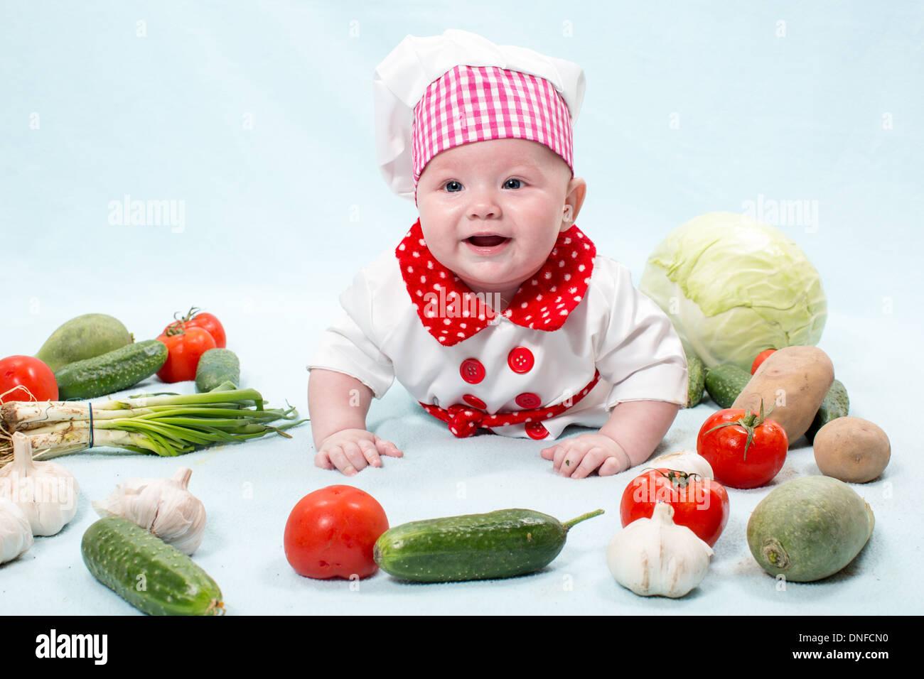 fdb0ede505c Baby cook girl wearing chef hat with fresh vegetables. Use it for a child