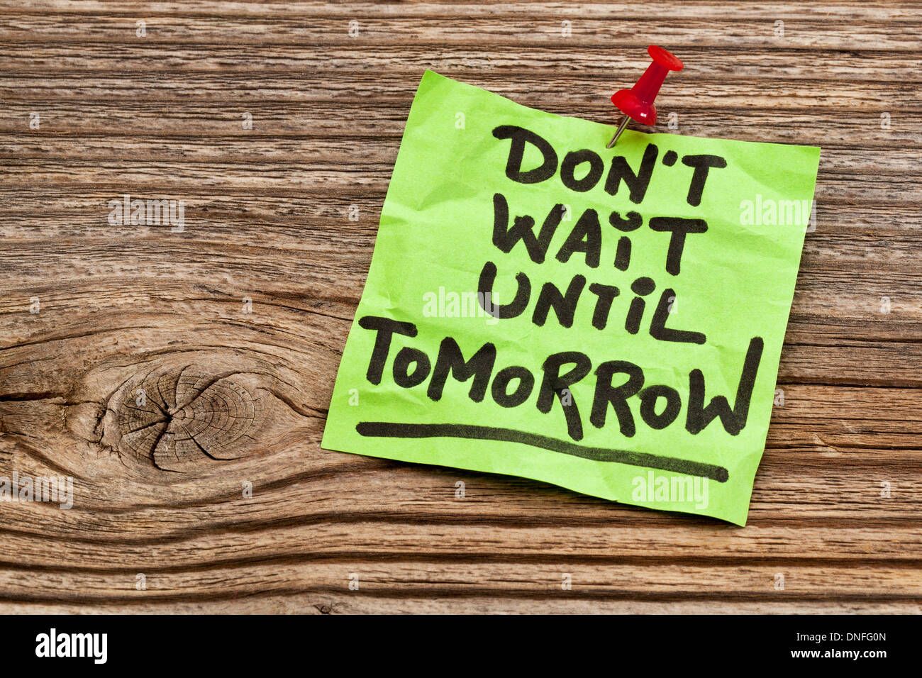 do not wait until tomorrow - motivational reminder - handwriting on sticky note against grained wood - Stock Image